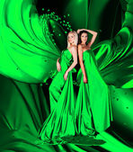 Two women in green dress with long hair and hearts on red draper — Stock Photo