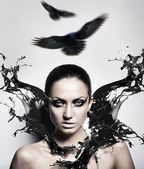 Sexy brunette woman with black splash and crows — Stock Photo