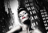 Attractive brunette woman with red lips in rainy city — Stock Photo