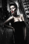 Sexy brunette woman with red lips in dark rainy city — Stock Photo