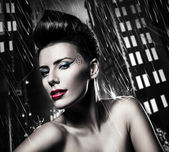 Sexy brunette woman with red lips in rainy city — Stock Photo
