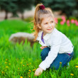 Stock Photo: Sweet beautiful girl sitting on a green meadow
