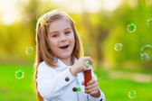 Smiling Little girl blowing soap bubbles — Stock Photo