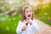 Happy Little girl blowing soap bubbles — Stock Photo