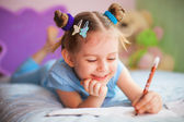 Happy little girl painting in her room — Stock Photo