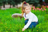 Sweet beautiful girl sitting on a green meadow — Stock Photo