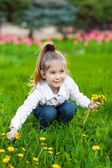 Happy kid sitting on a green meadow — Stock Photo