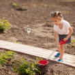 Little girl gardening in summer day