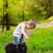 Little girl playing with dog in summer day — Stok fotoğraf