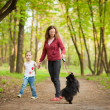 Mother and child walking playing with dog — Foto Stock