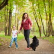 Mother and child walking playing with dog — Stockfoto