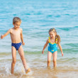 Happy kids playing at the beach shore — Stock Photo