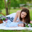 Happy mother and baby resting in summer park — Stock Photo #10581440