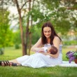Happy  mother and baby resting in summer park — Stock Photo