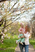 Mother and daughter walking in spring garden — Stock Photo