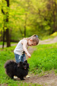 Little girl playing with dog in summer day — Stock Photo