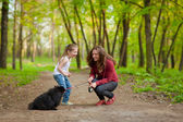 Mother and child walking playing with dog — Stock Photo