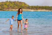 Mother with children running at the beach — Stock Photo