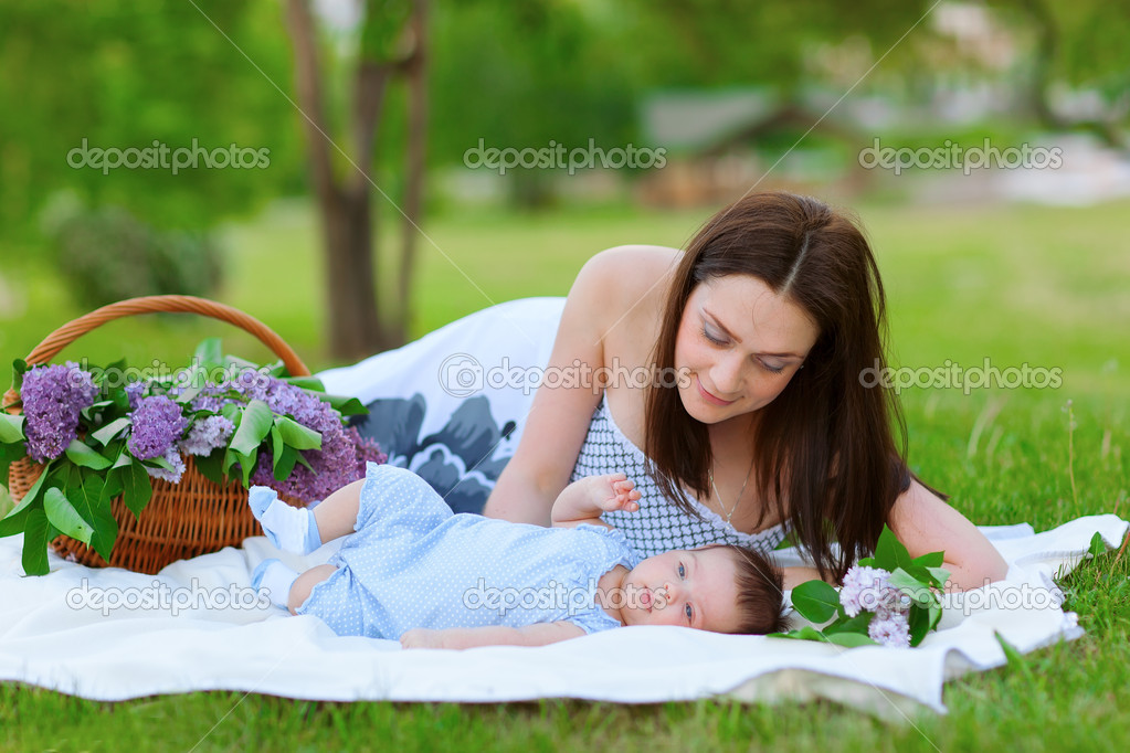Mother and baby resting in summer park with lilac bouquet — Stock Photo #10581440