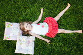 Little girl resting on pillows in summer garden — Stock Photo