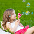 Cute child with lollipop resting on the grass — Stock Photo