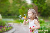 Cute curly girl with soap bubbles — Stock Photo