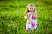 Sweet blonde girl smelling flowers on the meadow — Stock Photo