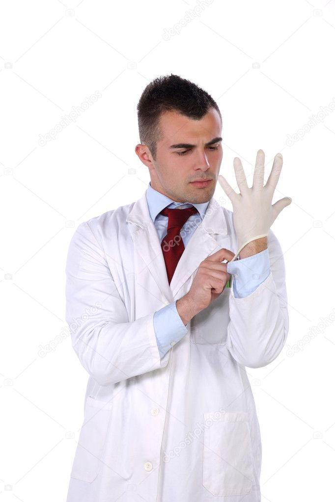 Young doctor standing and putting on his rubber glove — Stock Photo #10581843