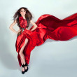 Flexible girl moves in a red long dress — Stock Photo #9826167