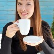 Stock Photo: Girl holding cup of drink and smiled pleasantly