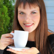 Stock Photo: Girl holding cup of teand smiled pleasantly