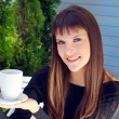 Stock Photo: Girl holding cup of coffee and smiled pleasantly