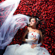 Bride is lying in flowerbed — Stock Photo #9826546