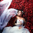 Bride is lying in flowerbed — Stock Photo