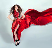 Flexible girl moves in a red long dress — Stock Photo