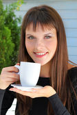 Girl holding a cup of tea and smiled pleasantly — Stock Photo