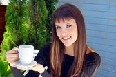 Girl holding a cup of coffee and smiled pleasantly — Stock Photo