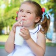 Girl drinking a milkshake through a straw - Stock Photo