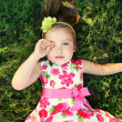 Foto Stock: Girl in bright dress lying on ground and closes her eyes