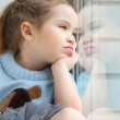 Baby girl sitting on the windowsill and looking out the window — Stock Photo
