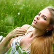Stock Photo: Girl in white dress lying in grass