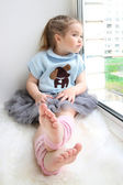 Baby girl sitting on the windowsill — Stock Photo
