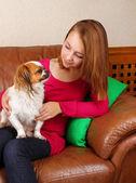 ソファの上に座っている犬を持つ少女 — ストック写真