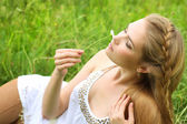 Girl lying in the grass with chamomile — Stock Photo