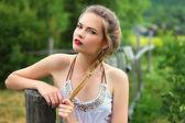 Girl in a garden near a wooden fence — Stock Photo