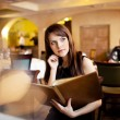 Girl with a menu in a restaurant — Stock Photo