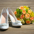 Wedding bouquet & shoes on wooden platform — Stock Photo #9842233