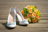 Wedding bouquet & shoes on a wooden platform — Stock Photo