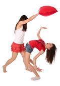 Two girls fighting on the pillows — Stock Photo