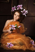 Girl with lilac lilies in her hair — Stockfoto